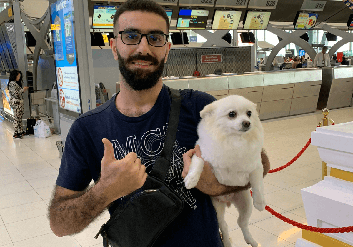a happy dog owner at departure day at Suvarnabhumi airport thailand by Relo4Paws